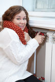 Smiling woman turning thermostat Royalty Free Stock Photo