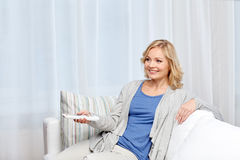 Smiling woman with tv remote control at home Stock Image