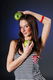 Smiling woman with two green apples. In her hand on blue background Royalty Free Stock Image