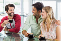 Smiling woman and two men having cup of coffee Stock Images