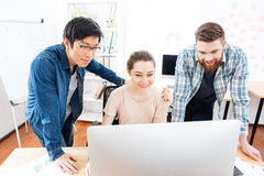 Smiling woman and two men working with computer in office Stock Photos