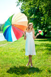 Smiling woman with two rainbow umbrellas, outdoors Royalty Free Stock Photos