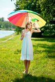 Smiling woman with two rainbow umbrellas, outdoors Royalty Free Stock Images