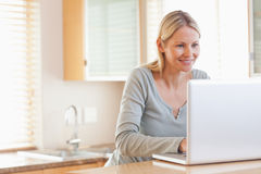 Smiling woman typing on her laptop Royalty Free Stock Photo
