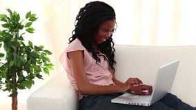 Smiling woman typing on a laptop Royalty Free Stock Image