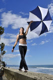 Smiling woman with umbrella. Young woman smiles at camera with umbrella Royalty Free Stock Image