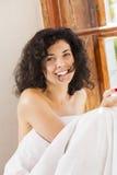 Smiling woman under blanket bite hair perm Stock Photos