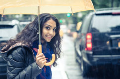Smiling woman under the rain covering with umbrella Royalty Free Stock Photos