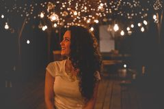 Smiling Woman Under String Lights royalty free stock photo