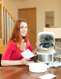 Smiling woman unpacking and reading user manual for new crock-po Royalty Free Stock Photography