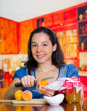 Smiling woman unpeeled a little peach with a big knife, firts step of peach jam Stock Images