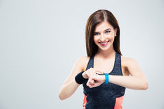 Smiling woman using activity tracker. Over gray background and looking at camera Royalty Free Stock Image