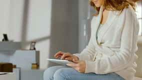Smiling woman using app on tablet PC at home, chatting online, watching movies Stock Photo