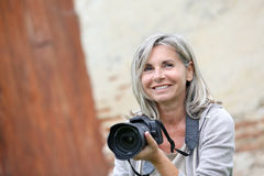 Smiling woman using camera outdoor Stock Photo