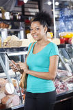 Smiling Woman Using Cell Phone In Grocery Shop Royalty Free Stock Photos