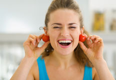 Smiling woman using cherry tomato as earrings Royalty Free Stock Photography
