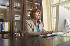 Smiling Woman Using Computer In Study Room Stock Photos