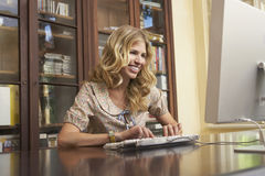 Smiling Woman Using Computer In Study Room Royalty Free Stock Image