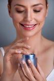 Smiling woman using cream Stock Image