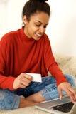 Smiling woman using credit card on laptop Stock Photos