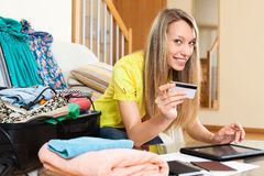 Smiling woman using credit card for reserving plane ticket Stock Photos
