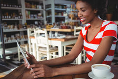 Smiling woman using digital tablet in cafe Royalty Free Stock Photo