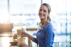 Smiling woman using digital tablet at counter in café Stock Photos