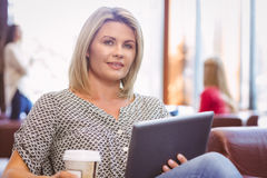 Smiling woman using digital tablet and holding disposable cup Stock Photography