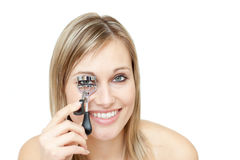 Smiling woman using an eyelash curler Royalty Free Stock Photo