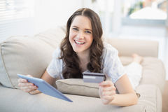 Smiling woman using her credit card to buy online Royalty Free Stock Photos