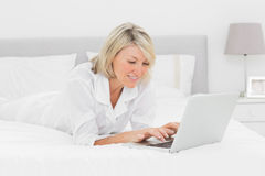 Smiling woman using her laptop on her bed Stock Image