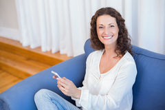 Smiling woman using her mobile phone. In the living room Stock Photography