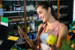 Smiling woman using her phone while buying fruits in organic section Stock Images
