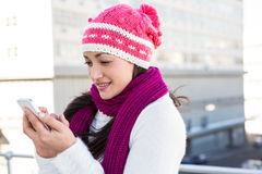 Smiling woman using her smartphone. Outside Stock Photo