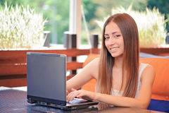 Smiling woman using laptop in cafe Royalty Free Stock Images