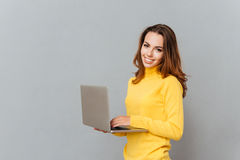 Smiling woman using laptop computer and looking at camera Stock Images