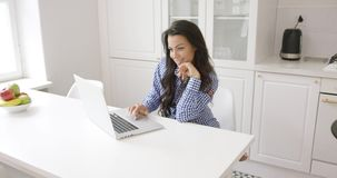 Smiling woman using laptop in kitchen stock footage