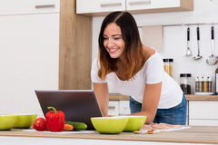 Smiling Woman Using Laptop In Kitchen. Smiling Woman Using Laptop For Cooking Delicious Item In Kitchen Stock Photography