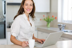 Smiling woman using laptop in the kitchen Royalty Free Stock Photo
