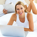 Smiling woman using a laptop lying on bed Royalty Free Stock Images