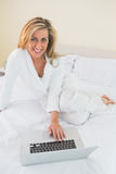 Smiling woman using a laptop lying on her bed stock photo