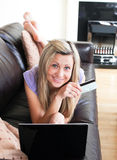 Smiling woman using a laptop lying on a sofa Royalty Free Stock Image