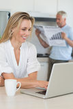 Smiling woman using laptop with partner standing with the paper Stock Images