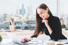 Smiling woman using laptop. Portrait of attractive smiling businesswoman using laptop computer at office desk with coffee cup, paperwork and other items. City Stock Photography