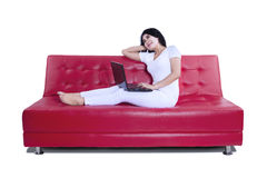 Smiling woman using laptop on red sofa Royalty Free Stock Photography