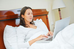 Smiling woman using laptop sitting in bed Royalty Free Stock Images
