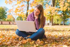 Smiling Woman Using Laptop Sitting on Ground Alone Stock Photo