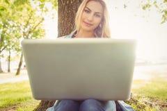 Smiling woman using laptop while sitting under tree Stock Photos