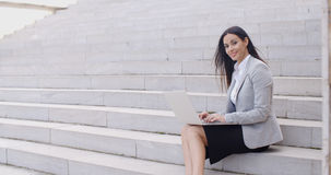 Smiling woman using laptop on stairs Royalty Free Stock Image
