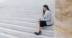 Smiling woman using laptop on stairs Stock Photography